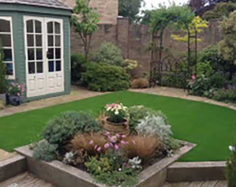 fake grass in garden with flower bedding
