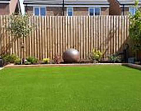 bright green artificial grass in garden with timber fencing