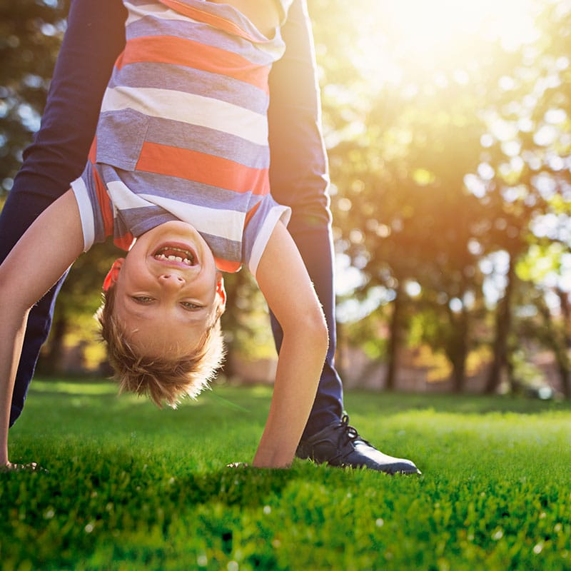 Upside down boy doing handstand on artificial grass in the garden, helped by man behind him