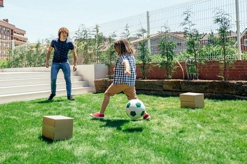 Father and son playing soccer in the garden