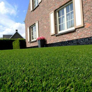 fake grass lawn in front of country house