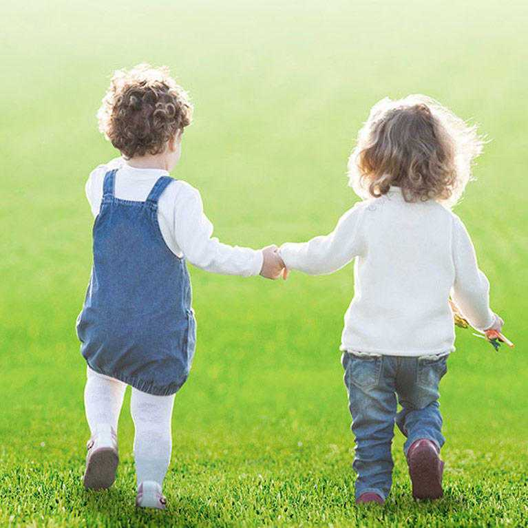 two toddlers hold hands as they run on fake grass