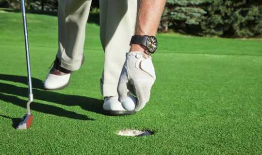 retrieving a golf ball from the hole on an artificial grass putting green