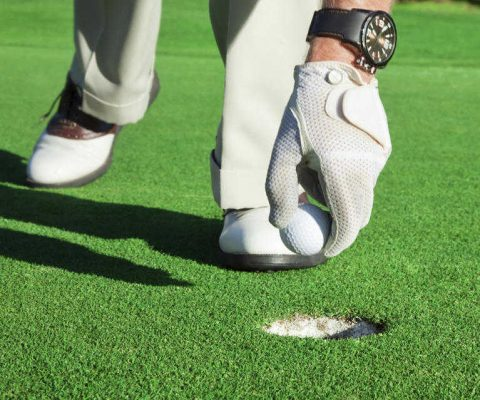 man takes golf ball out of hole laid with fake grass