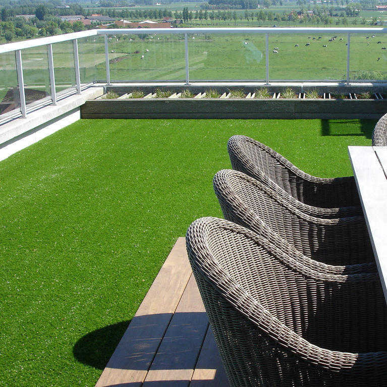 vibrant fake grass laid on balcony with view of farm land