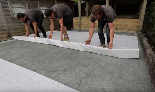 3 men rolling out protective geotex membrane
