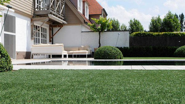 dark green fake grass by garden swimming pool