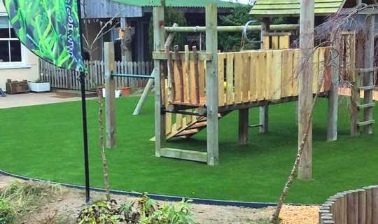fake grass laid at school around timber play ground