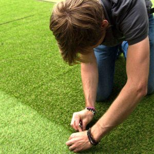 man joining artificial grass together