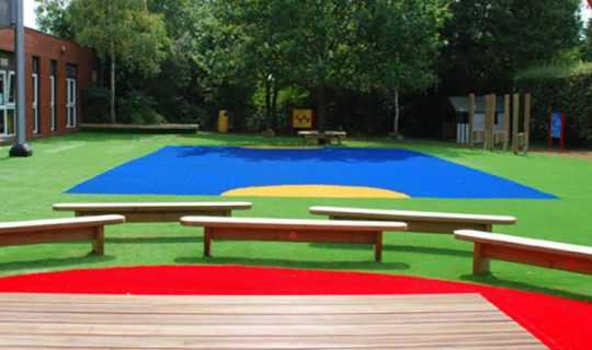 school play area with coloured fake grass and benches