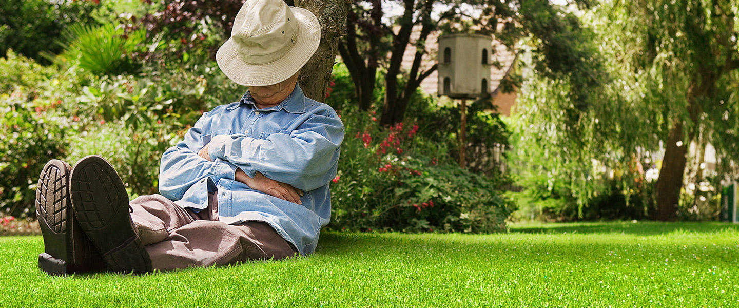 man sat napping on artificial grass under a tree