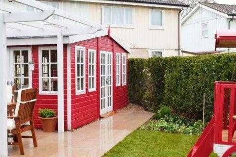 red summer house shed surrounded with fake grass
