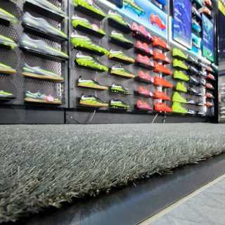 artificial grass laid in sport store with football boots