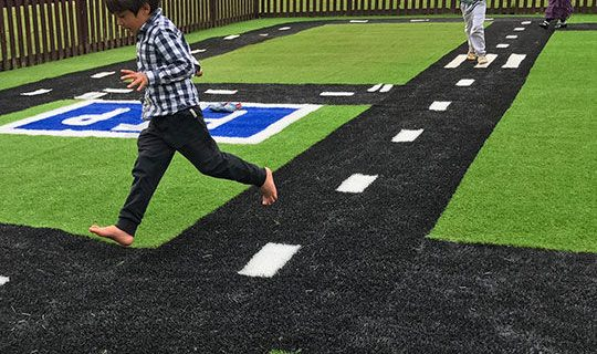 Fake grass road with children running